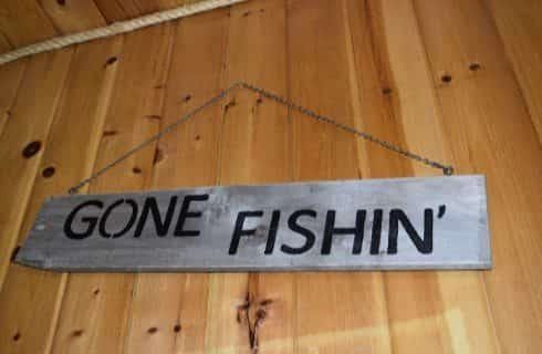 Large gray wood plank sign that says Gone Fishin' hanging on a light wood paneled wall