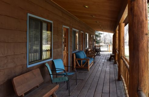 Close up view of a lodge's large porch with wooden furniture and metal chairs