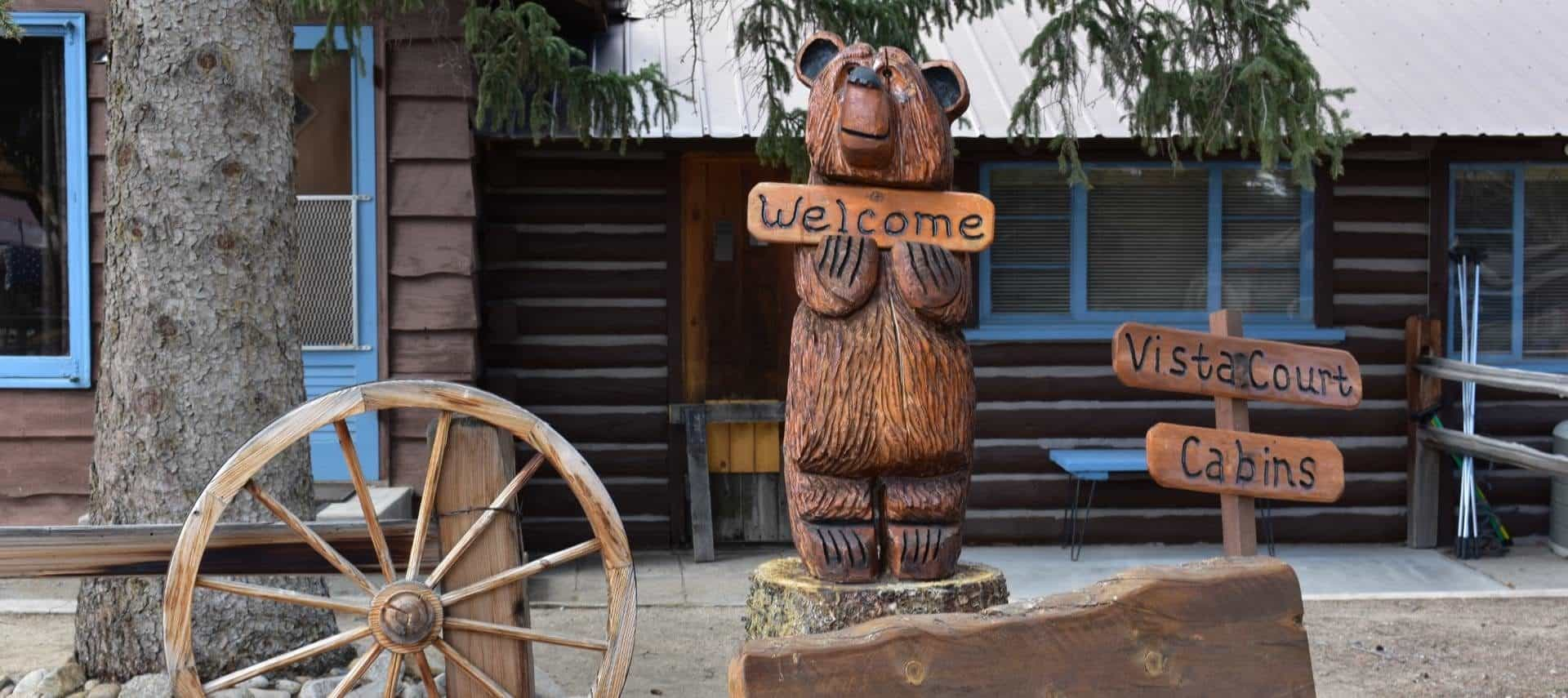 Wooden cottage with blue painted door and trim with a carved wooden bear holding a welcome sign