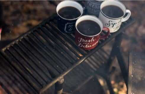 Four coffee cups filled with coffee sitting on top rack of fire pit grill