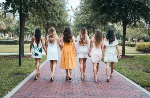 Six ladies wearing dresses walking down a brick paver walkway, all with their backs to the camera