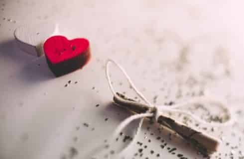 Two wooden hearts, one white and one red, next to a small rolled up note tied with white string
