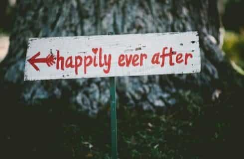 White wooden sign with happily ever after painted in red