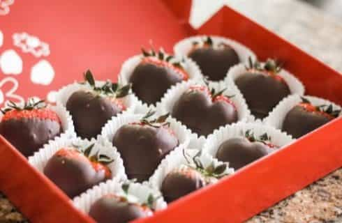 Chocolate covered strawberries in white wrappers organized in red box
